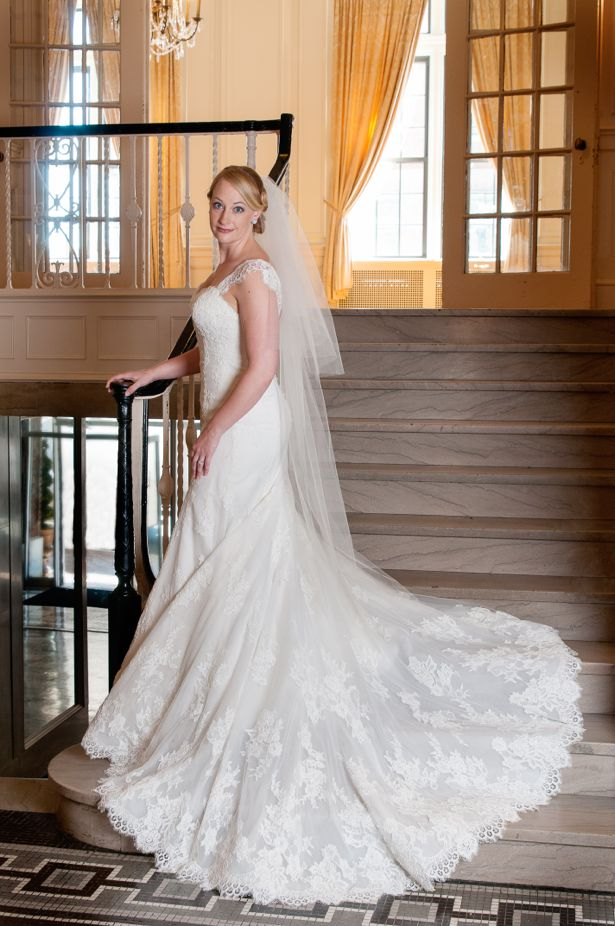 Bridal portraits - young woman in lace wedding gown standing on grand staircase.