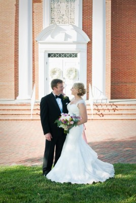 Newly married couple stands in front of church