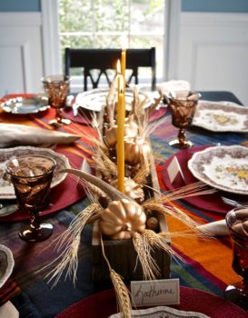 A wood box centerpiece with pumpkins,wheat, antlers, and acorns is the perfect fall centerpiece for your Thanksgiving table.