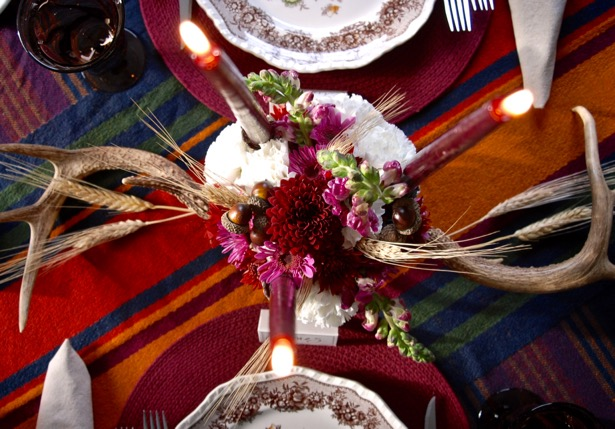 Set a rustic Thanksgiving table with antlers, mums, wheat, and burgundy accents.