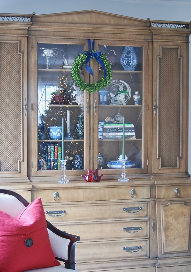 My china cabinet decorated for Christmas with boxwood wreath