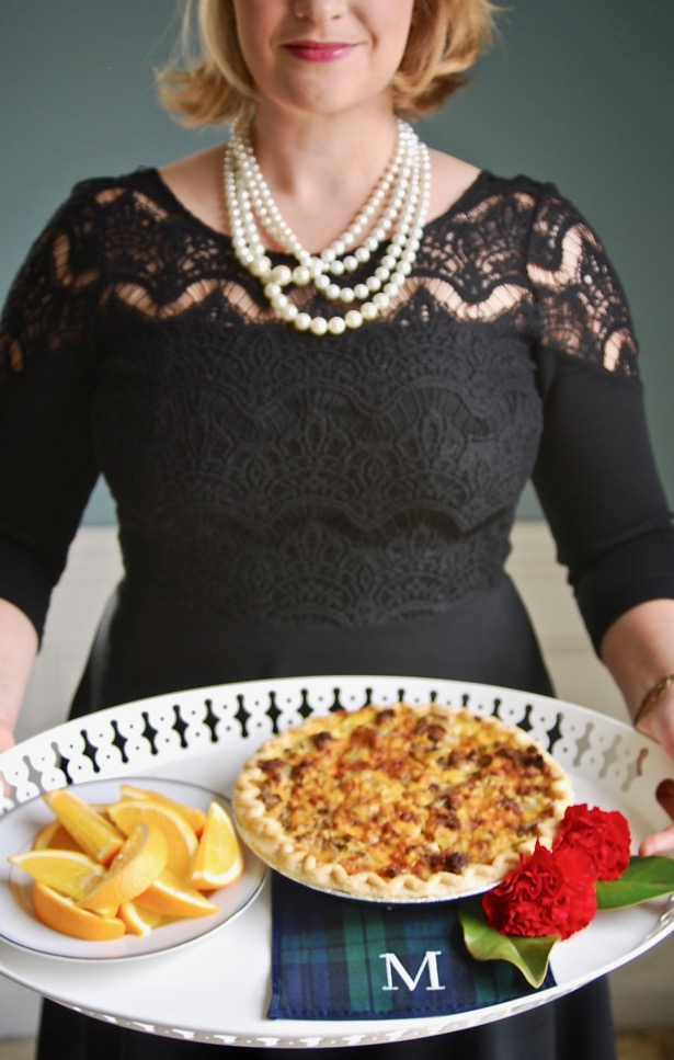 Holiday Hosting Hacks: Woman in black dress holds tray with Christmas brunch of quiche and oranges