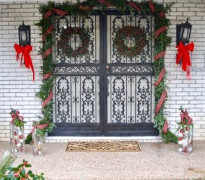 A traditional Christmas Front Door with plaid ribbon, garland, holly wreaths, and lanterns