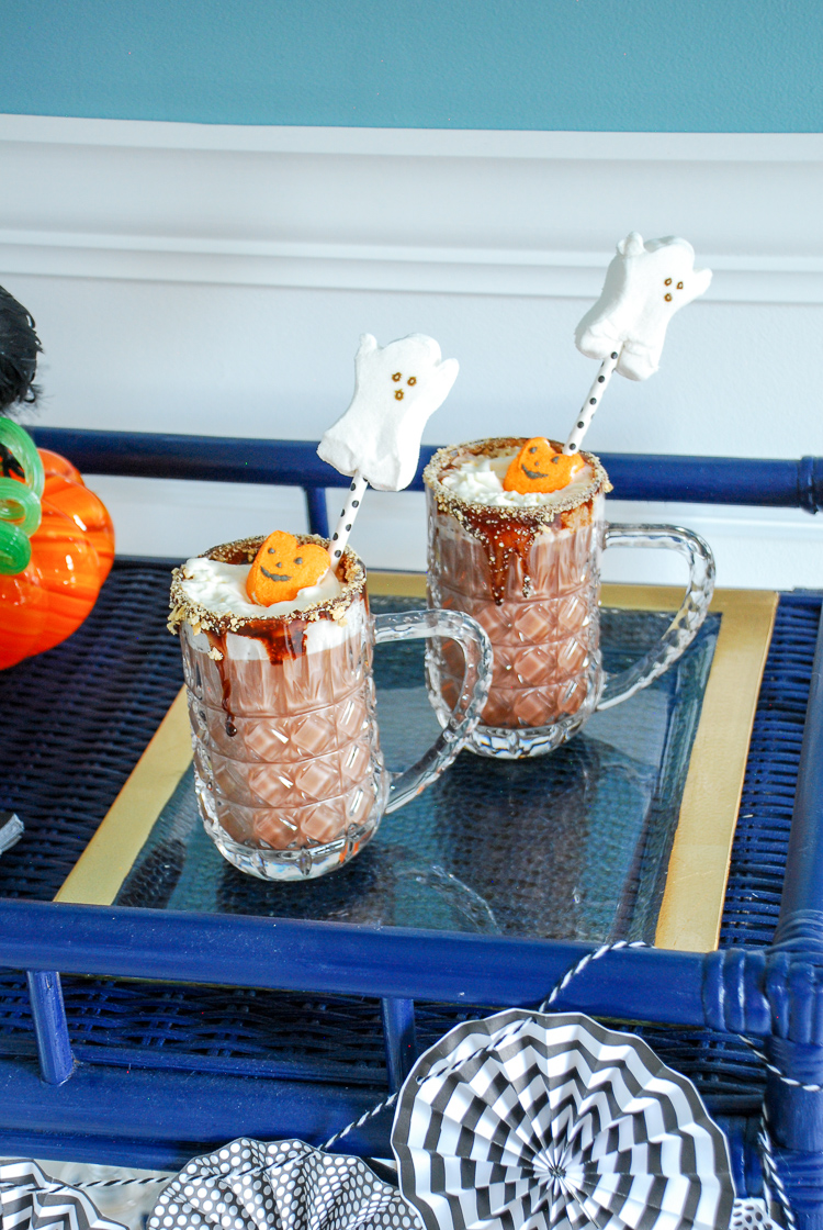 Embrace your inner ghoul and indulge your sweet tooth with this Halloween spooked cocoa. Topped with pumpkin and ghoul peeps, whipped cream, and a chocolate graham cracker rim it is sure to please kiddos and adults alike.