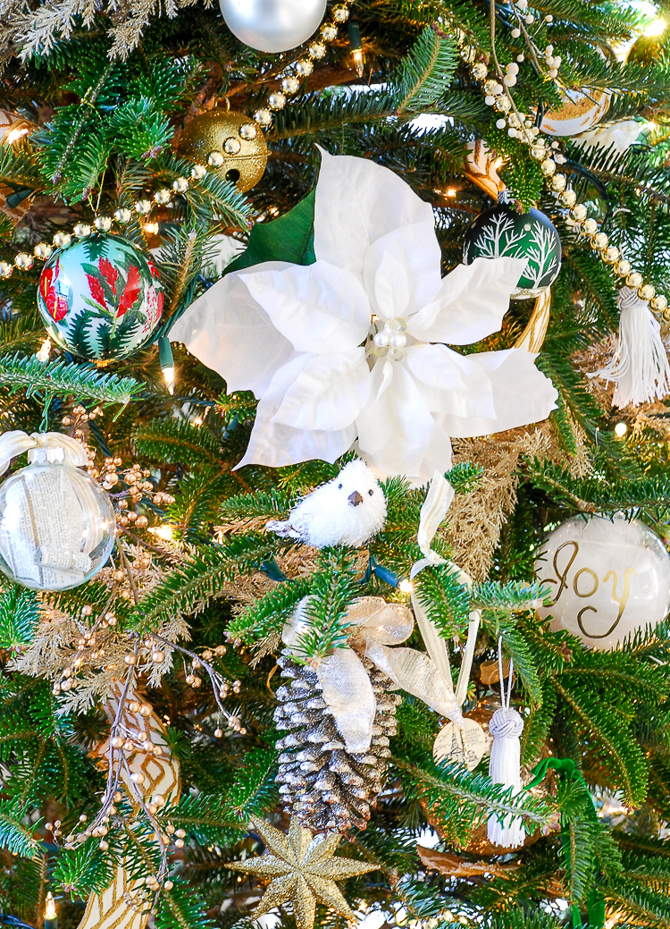 Green and gold Christmas tree decor with poinsettia, gold garland, pinecones, and tassel ornaments.