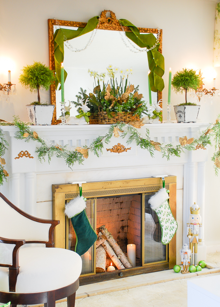 Green and gold Christmas mantel with paperwhites, topiaries, juniper, charteruse velvet ribbon, and reindeer.