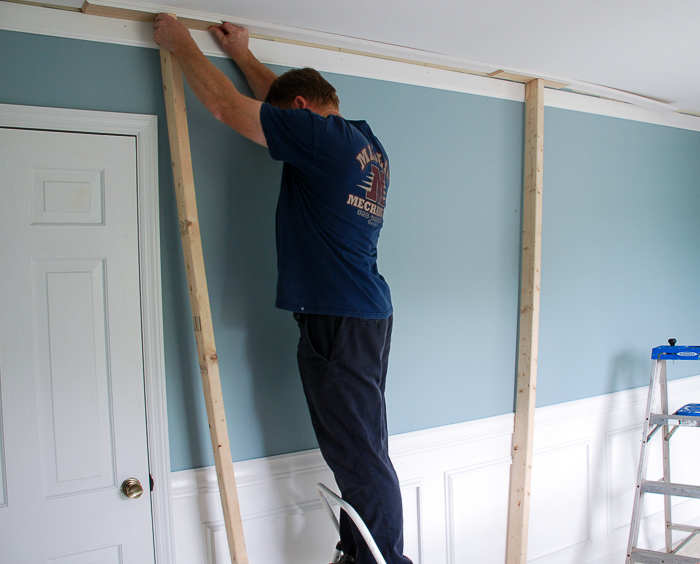 Man installs DIY crown molding in dining room.