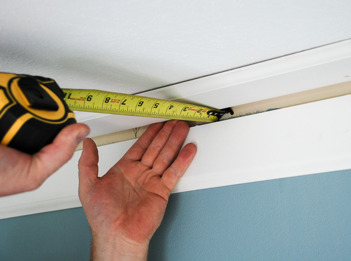 Measuring tape shows distance between wall and crown molding