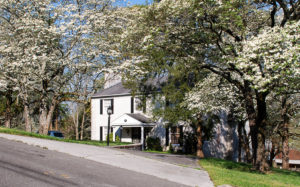 Naming your house: white brick house with dogwood trees in bloom
