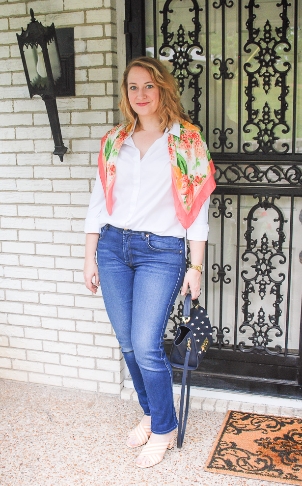 Blond woman wearing prepping wardrobe staples, including jeans and white button down with bright floral scarf around shoulders.