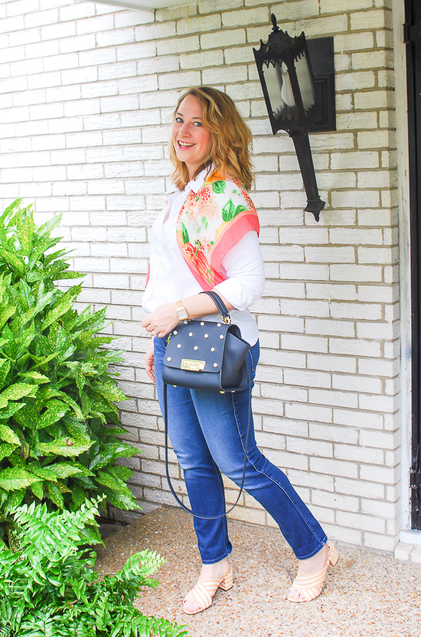 Blond woman in preppy wardrobe staples: white oxford, dark wash denims, heels, and scarf.