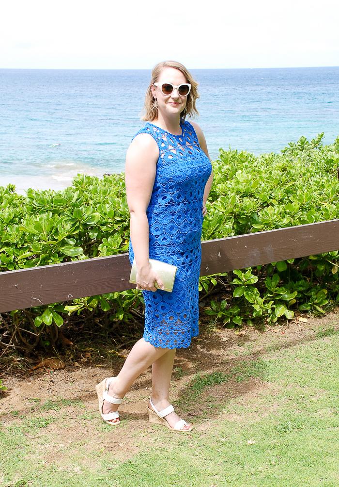 Wedding guest attire: blonde woman stands before ocean in blue crochet dress perfect for beach wedding.