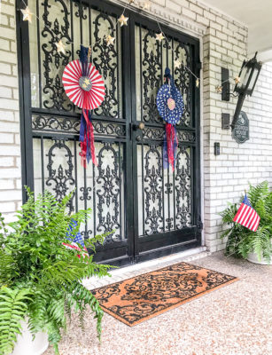July 4th decorated front door with red, white, and blue DIY patriotic rosettes and star twinkle lights.