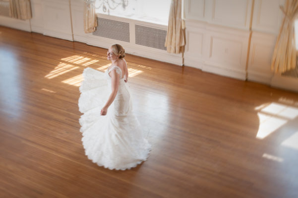 Bridal portrait of young woman in wedding dress dancing in ballroom.