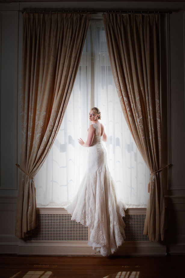 Bridal portraits of young woman in white lace wedding gown posing in front of window.