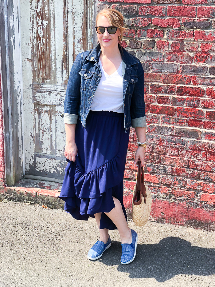 Blonde woman in casual summer skirt & sneakers look: blue ruffle skirt with jean jacket and blue slip-on sneakers posing in front of brick wall.