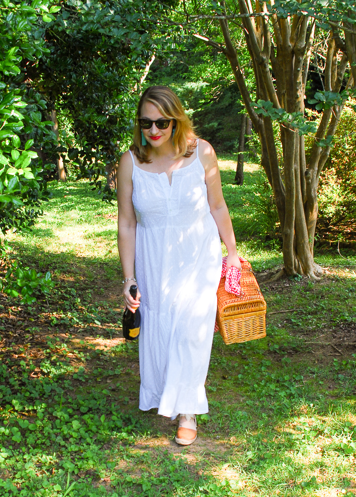 Blonde woman in white eyelet maxi dress walks in wooded area with picnic basket and champagne.