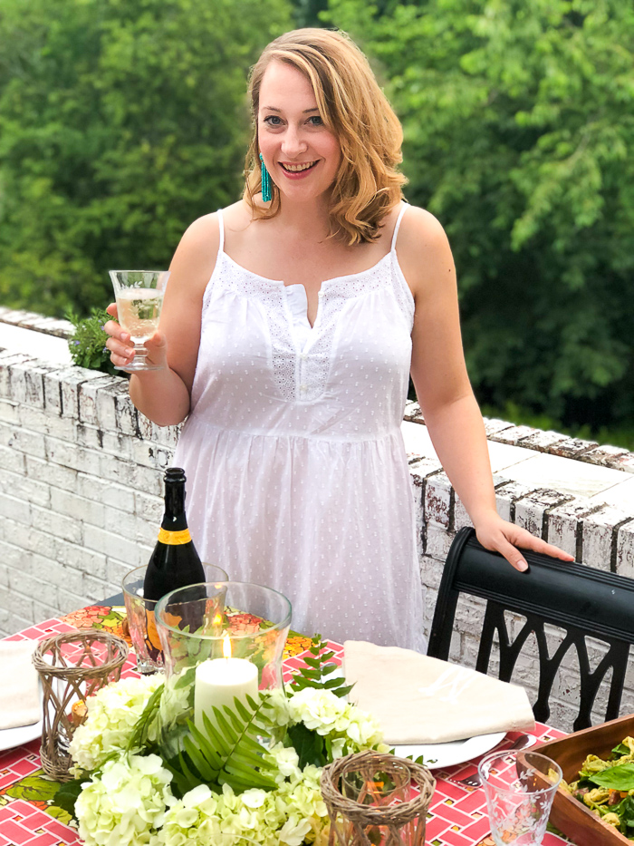 Blonde woman in white maxi dress enjoys al fresco summer dining with glass of bubbly.