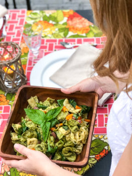 Woman carries pesto tortellini salad to summer al fresco dinner