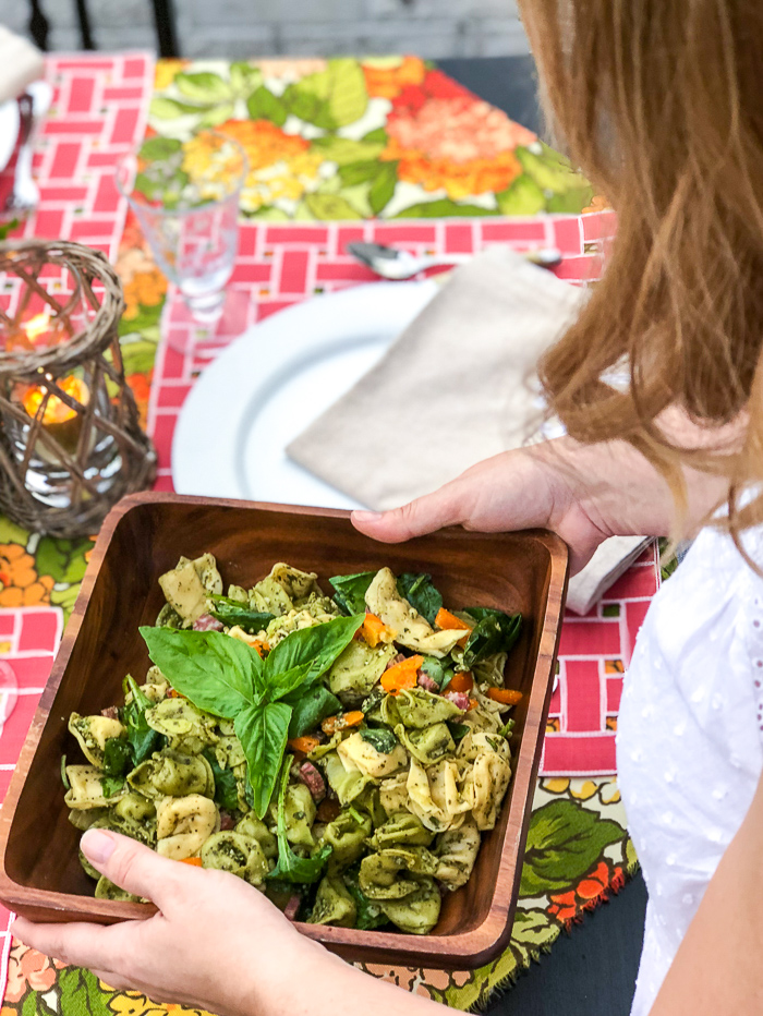 Woman carries pesto tortellini salad to summer al fresco dinner