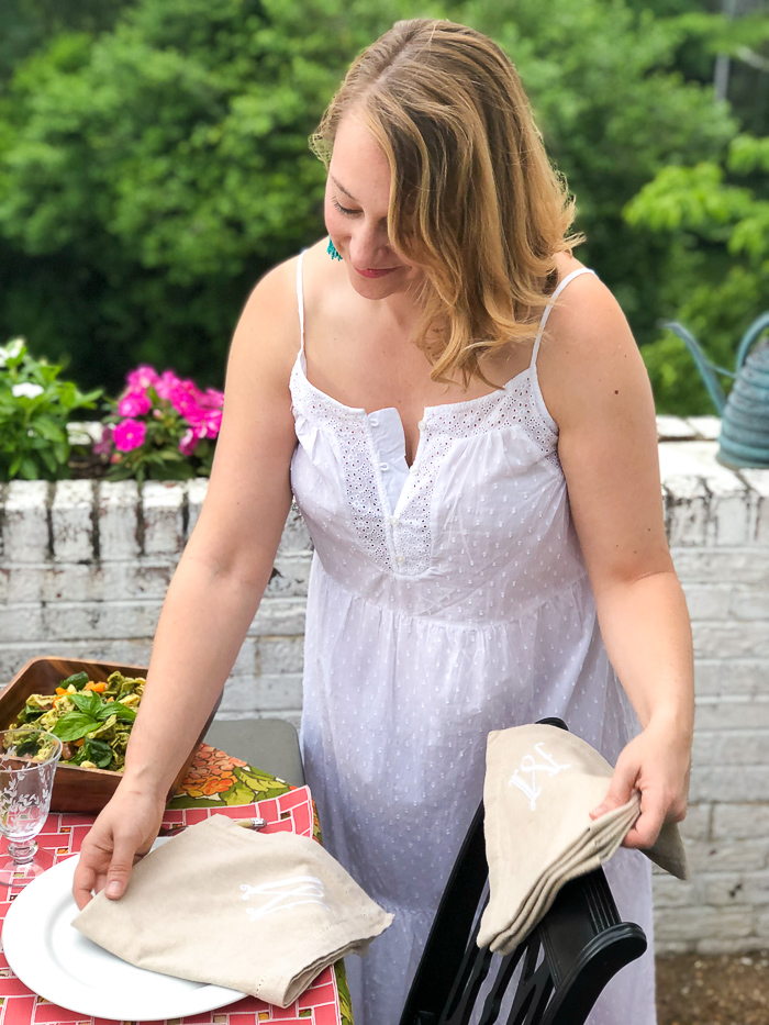 Blonde woman lays sets table for al fresco summer dining