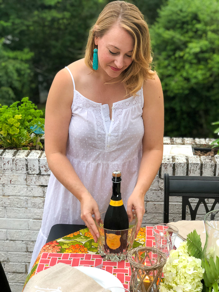 Blonde woman in white maxi dress places Prosecco on table for al fresco summer dining