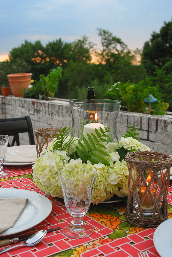 Sun sets behind table set for al fresco summer dining with hydrangea centerpiece