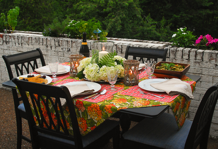 Table set for al fresco summer dining with hydrangea centerpiece and vibrant linens