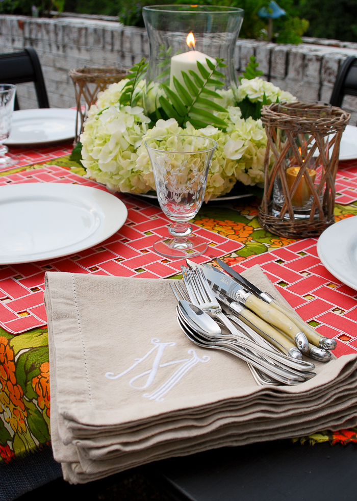 Table set for al fresco summer dining with hydrangea centerpiece and monogrammed napkins