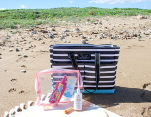 Striped beach bag in the sand with beach skin care products