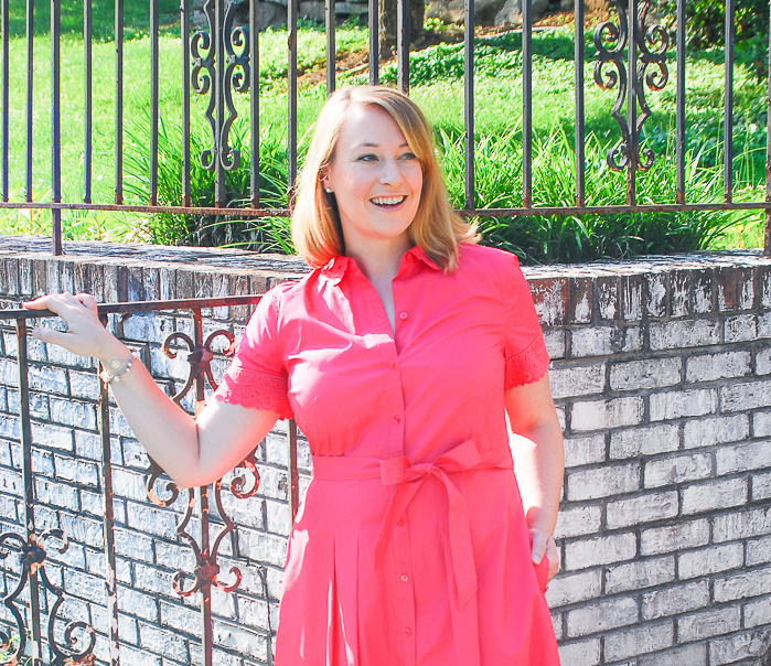 Blonde woman in front of gate wearing a pink shirtdress