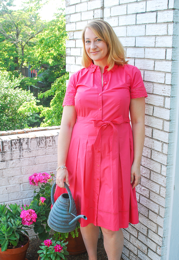 Blonde woman in pink shirtdress waters flowers on balcony