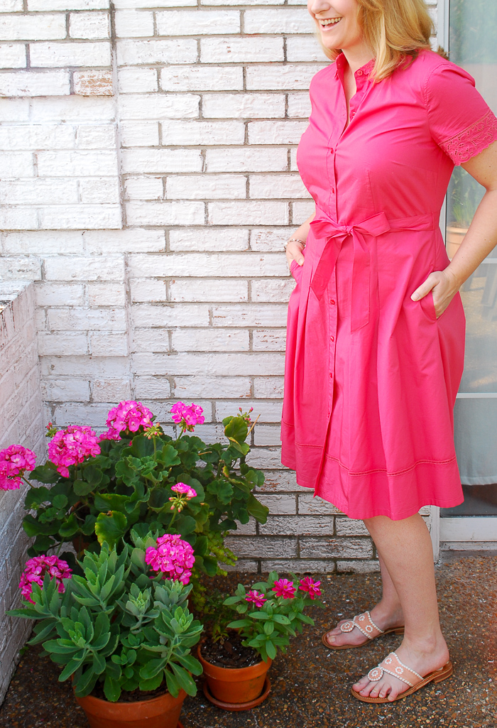 Blonde woman in pink shirtdress stands on balcony with flowers