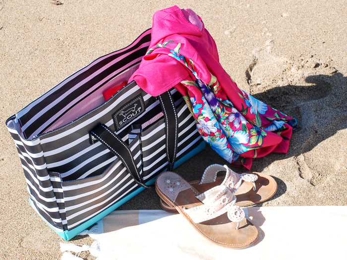 Summer essentials for the beach tossed in beach bag sitting in the sand