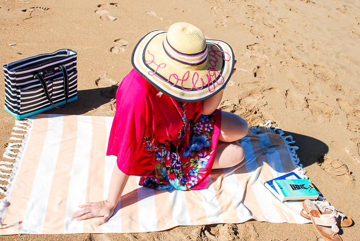 Woman on striped beach towel in floral pink coverup and sunhat - summer beach essentials