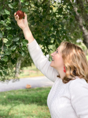 Partake in autumn adventures with this fall bucket list - Blonde woman reaching up to pick an apple.