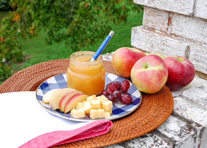 Cinnamon ginger applesauce recipe in small jar on rattan tray with sliced apples, grapes, and cheese.