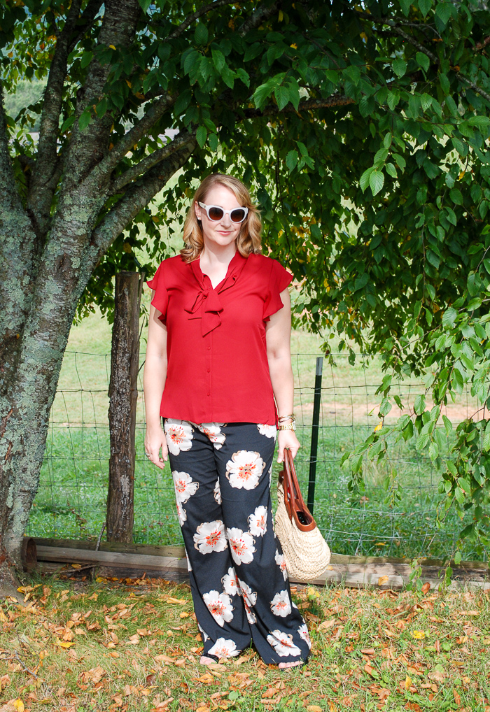 Blonde woman stands under tree in fall transition outfit of garnet blouse and palazzo pants