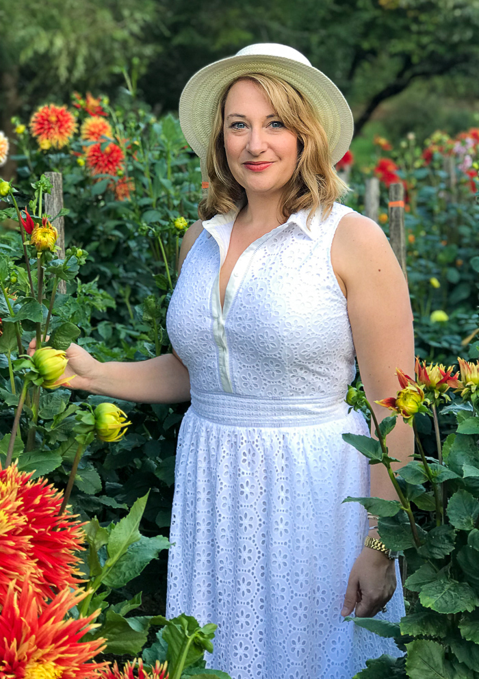 Thoughts on a gracious disposition - woman stands in white dress with hat surrounded by beautiful dahlias