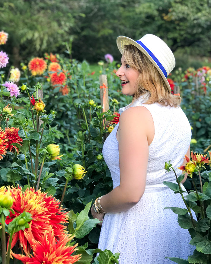 Thoughts on a gracious disposition - woman in white dress and hat stands in field of dahlias