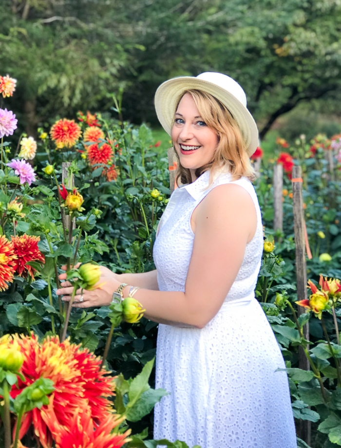 Gracious disposition: blonde woman in hat stands in field of dahlias