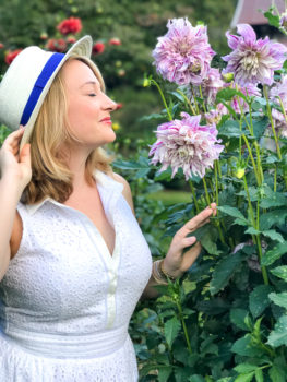 Blonde woman in white dress and hat smells purple dahlias