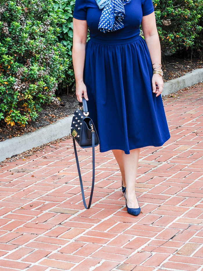 Blonde woman in navy work dress from gal meets glam with blue scarf tied in bow.