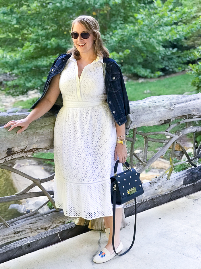 Transition summer staples to fall: blonde woman on bridge overlooking stream in little white dress with denim jacket