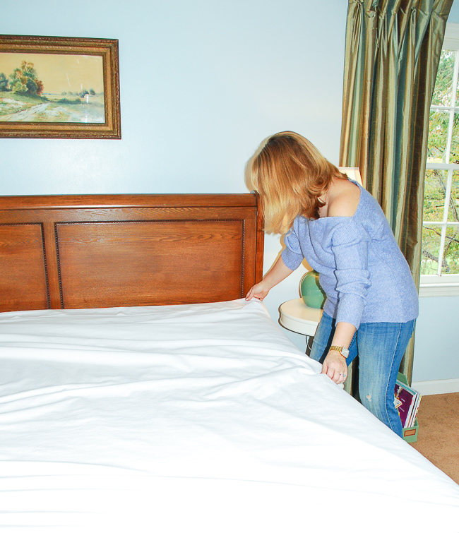 Woman making bed with white sheets from California Design Den