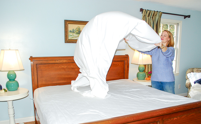 Woman flipping sheet to make the bed. A comfy bed for autumn starts with a great foundation - quality bed sheets.