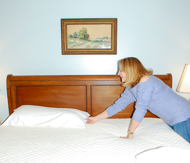 Woman lays pillow on bed to create coziest comfy bed