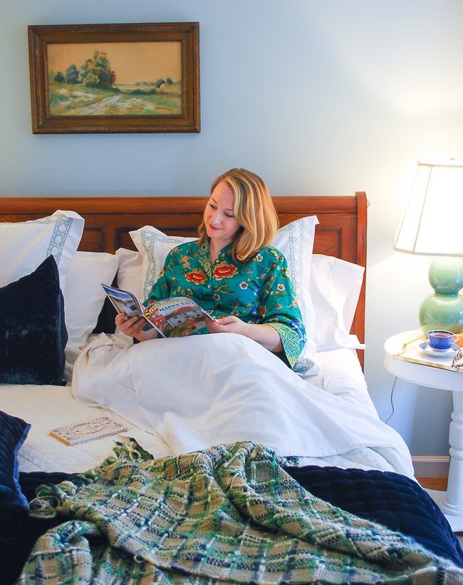 Woman reading magazine in comfy bed made with best bed sheets from California Design Den