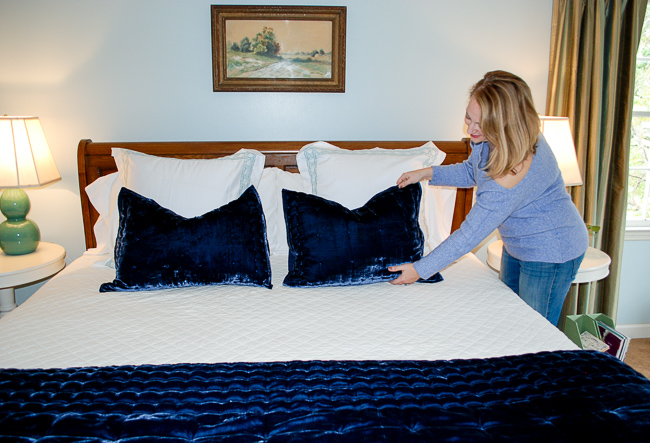 Woman places velvet pillow on comfy bed