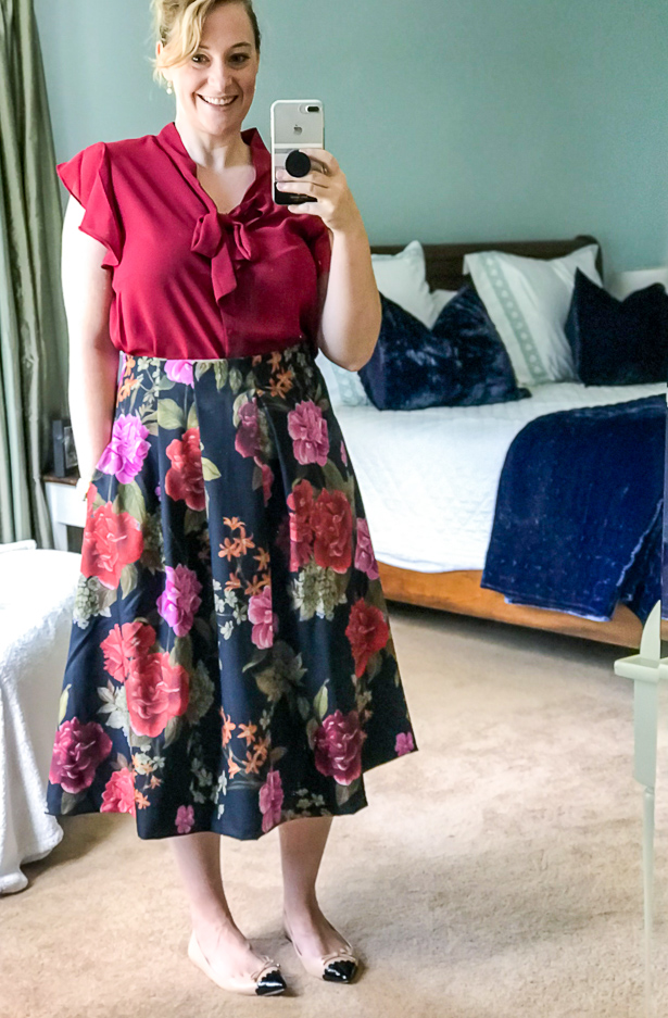 Selfie of woman in garnet top and fall floral midi skirt.